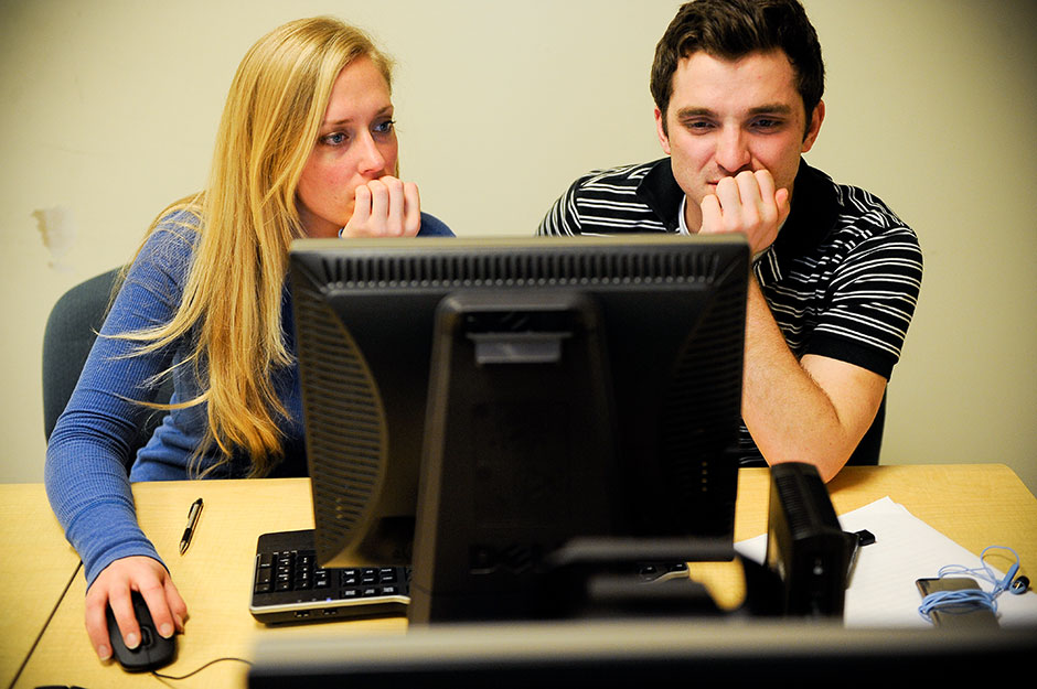 Graduate assistant Jennah Sontag and junior Dominic Caldarello review one of 75 stories submitted for publication.
