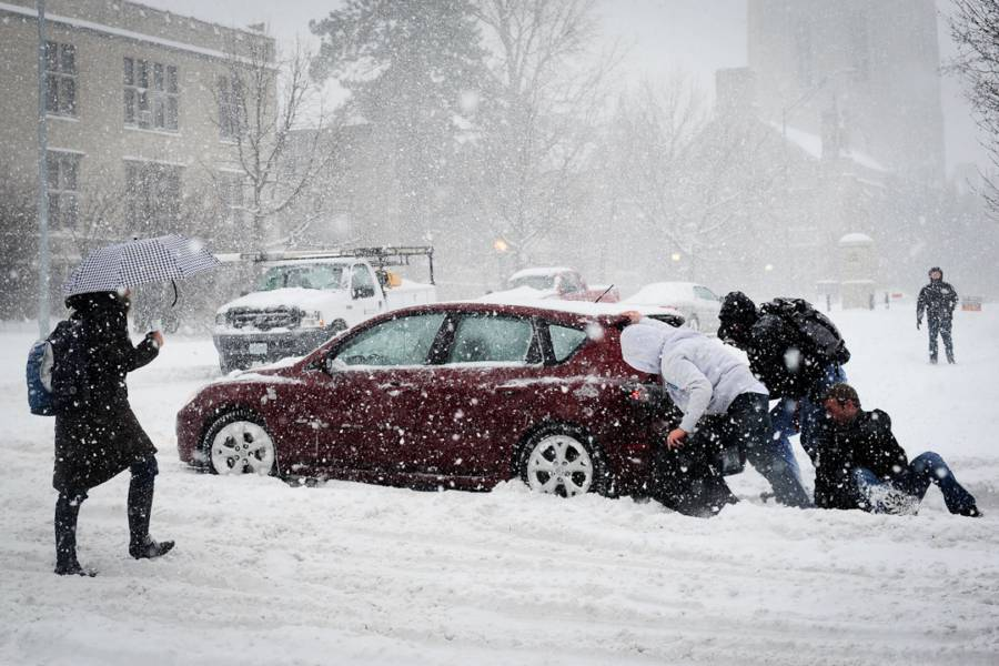 Students pushing car in snow