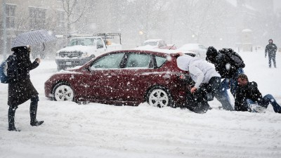 Students pushing car out of snow