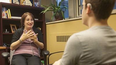 Angela Graves conversing with a student in sign language.