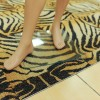 A barefoot mannequin stands on tiger-striped carpeting