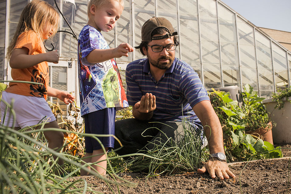 Doctoral student and children planting seeds
