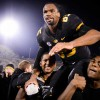 Football players carry teammate on their shoulders.