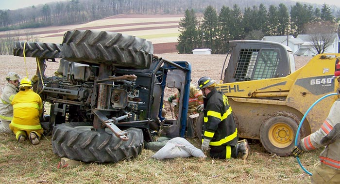 Firemen around a turned over tractor