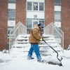 Campus Facilities employee Carolyn Kammerich shovels the steps in front of McReynolds Hall.