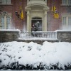 A Campus Facilities employee clears the steps outside the Residence on Francis Quadrangle with a snow blower.