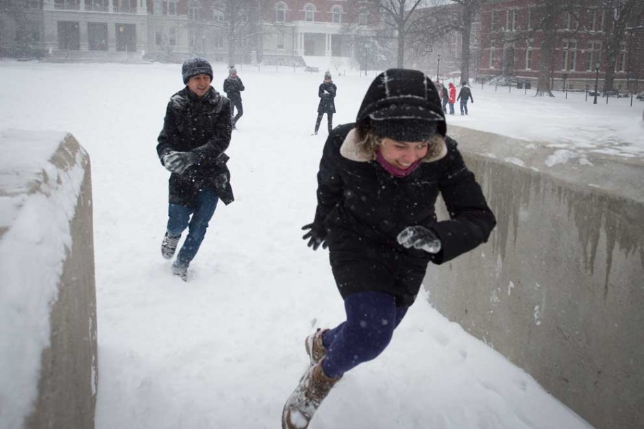 Students run between the Columns in a snow ball fight.