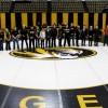 Students standing on wrestling mat.