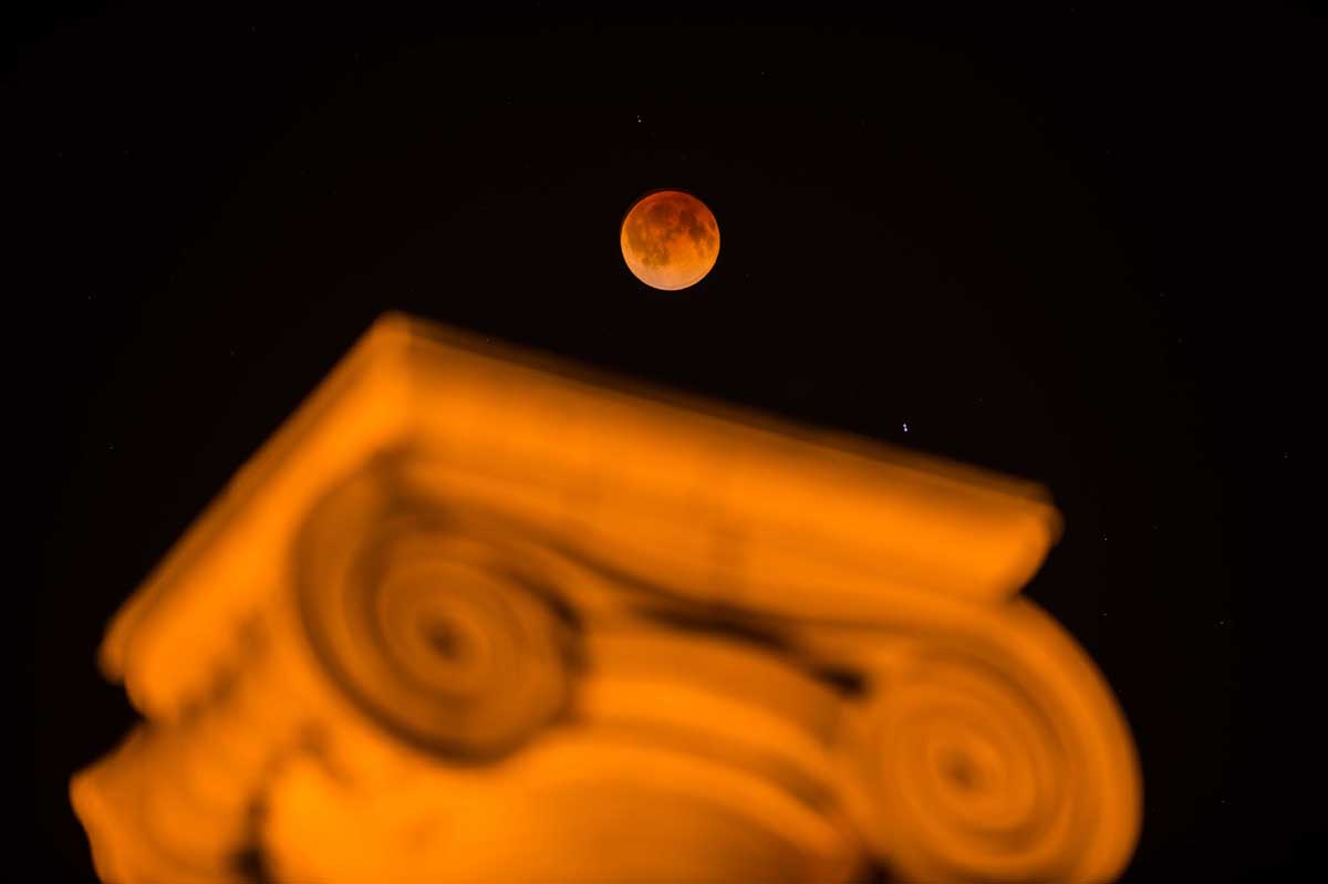 "Light from the sun refracts through Earth's atmosphere to cast a brownish-red hue on the moon, known as a ""blood moon."""