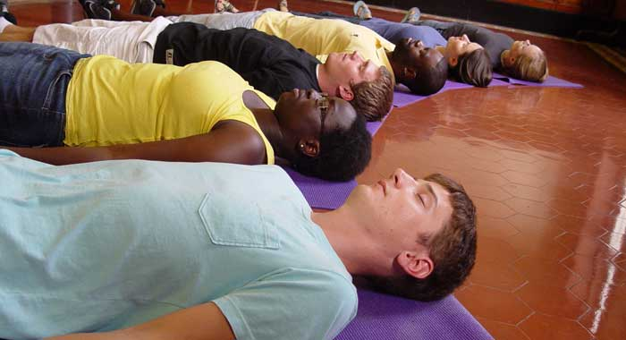Students lying on the floor, meditating.
