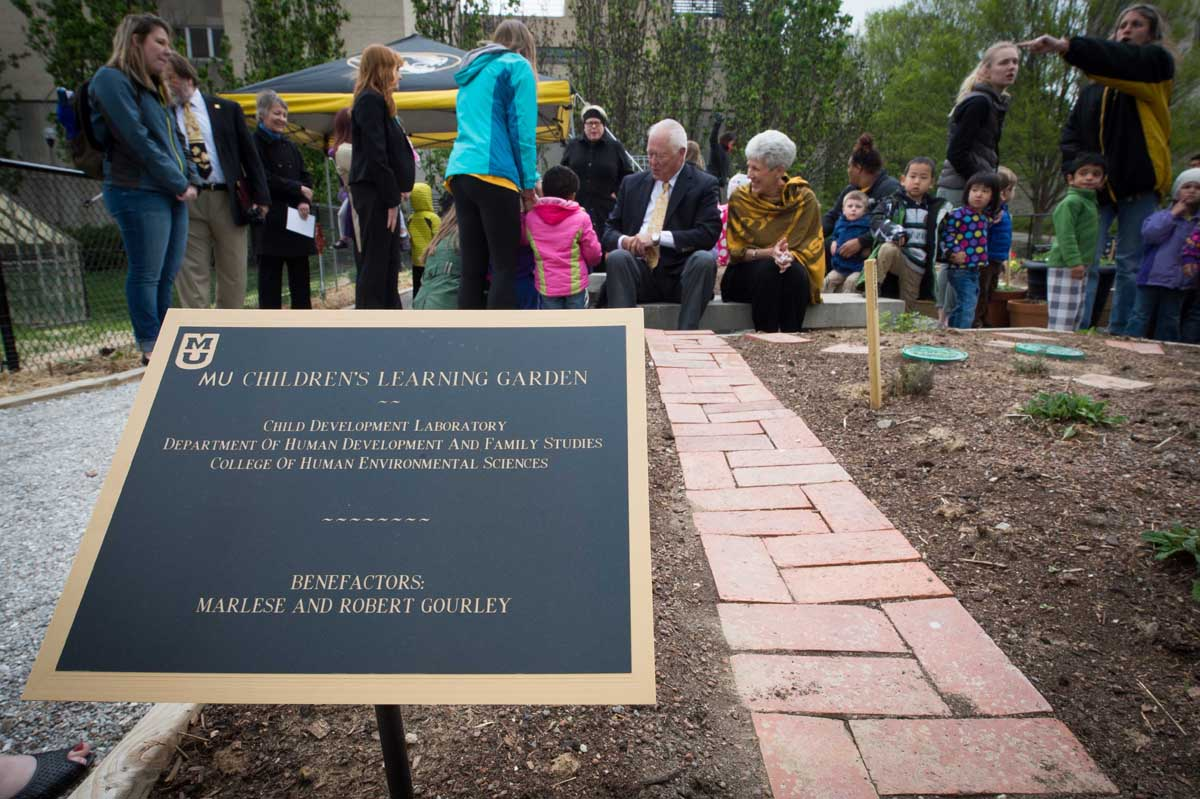 As the sign reads, our benefactors for the garden, Robert and Marlese Gourley, they are pictured in the background surrounded by the children, faculty, and staff from the CDL.