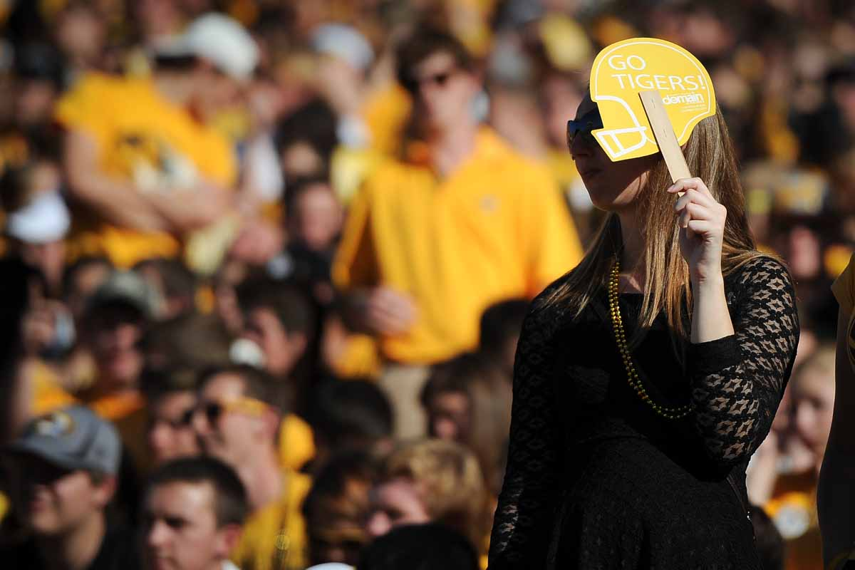 A Tiger fan shields her face from the sun during the first half of the game.