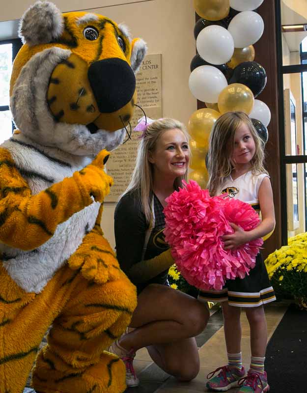 Truman poses for a photo with an MU cheerleader and an adoring fan.