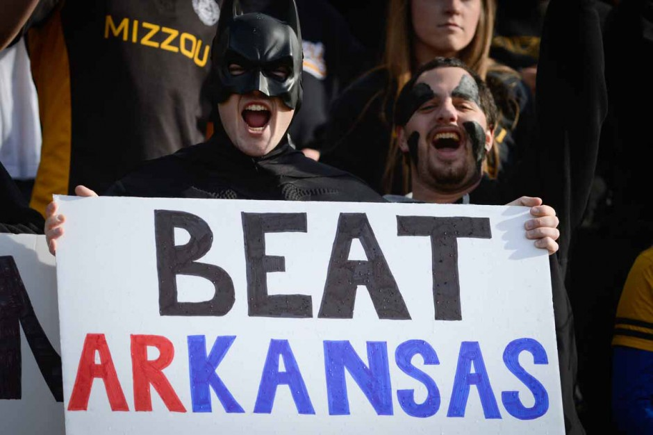 """Fans in Batman costumes holding sign that says """"Beat arKANSAS"""""""