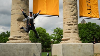 Student in cap and gown jumping from Columns.