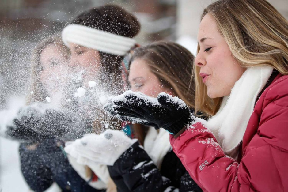 Ally Nuttall blows a handfull of snow into the air with her friends. Nuttall is a sophomore and spent part of her snowday playing in the snow before the snowball fight commenced. Photo by Hanna Yowell.