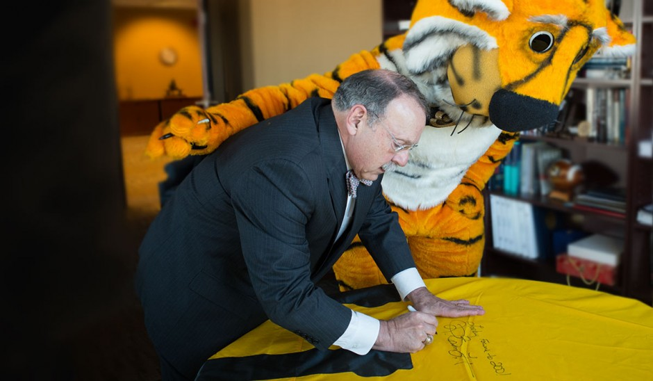 Chancellor Loftin and Truman the Tiger sign the 175th anniversary flag.