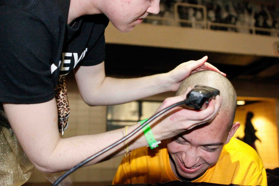 A hairdresser shaving a student's head.
