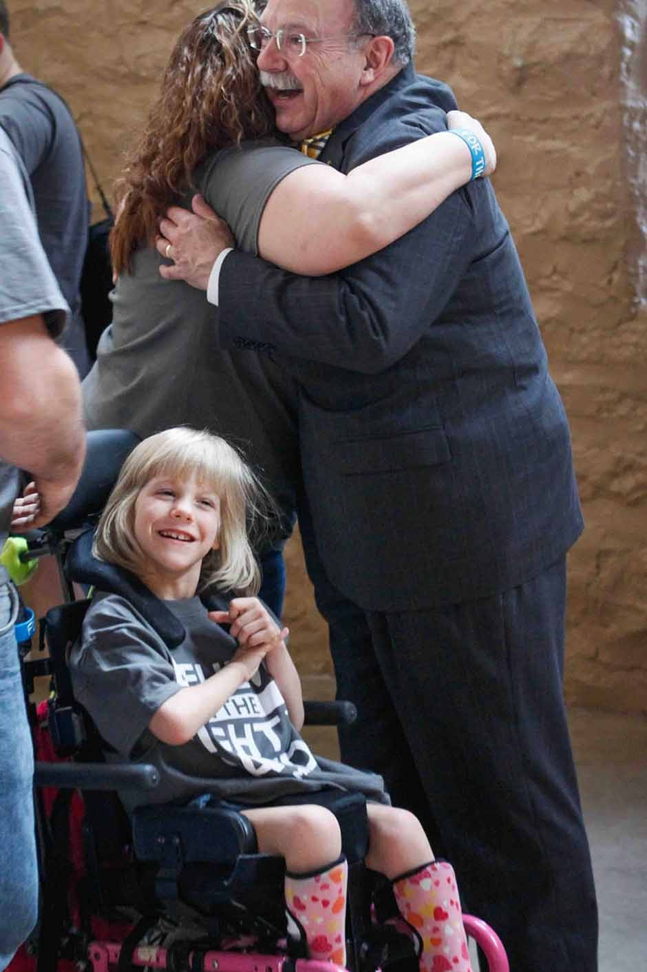 Loftin hugging a woman next to a smilig girl in a wheelchair.