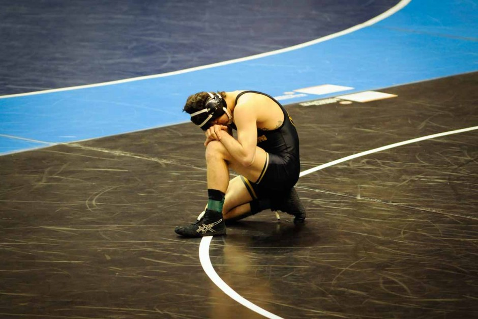 Sophomore Joey Lavallee kneels to the mat before his 8-6 win against Oklahoma's Justin DeAngelis in the 157-pound weight class.