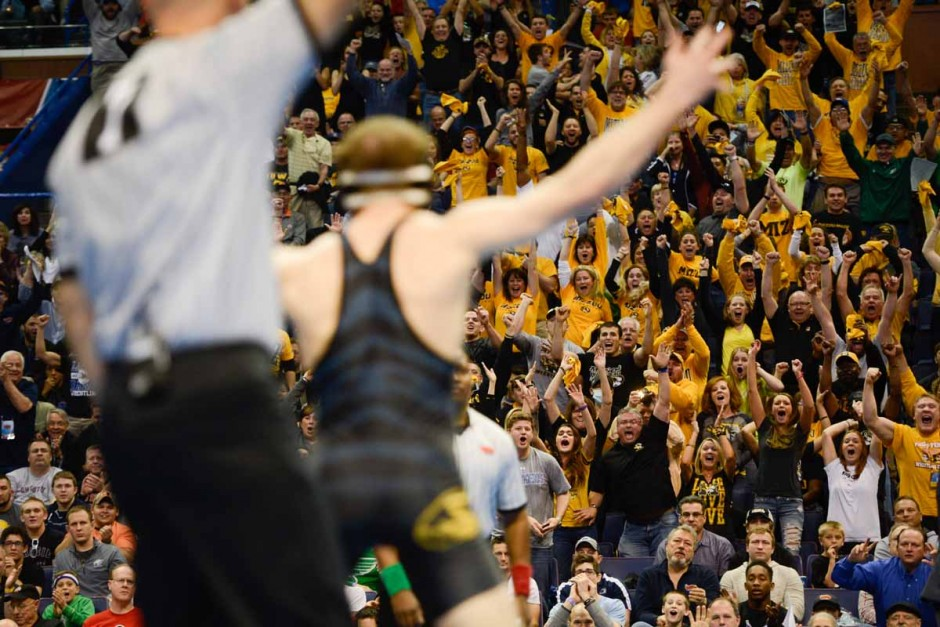 Drake Houdashelt raises his arms and faces Mizzou fans in celebration of being a national champion.