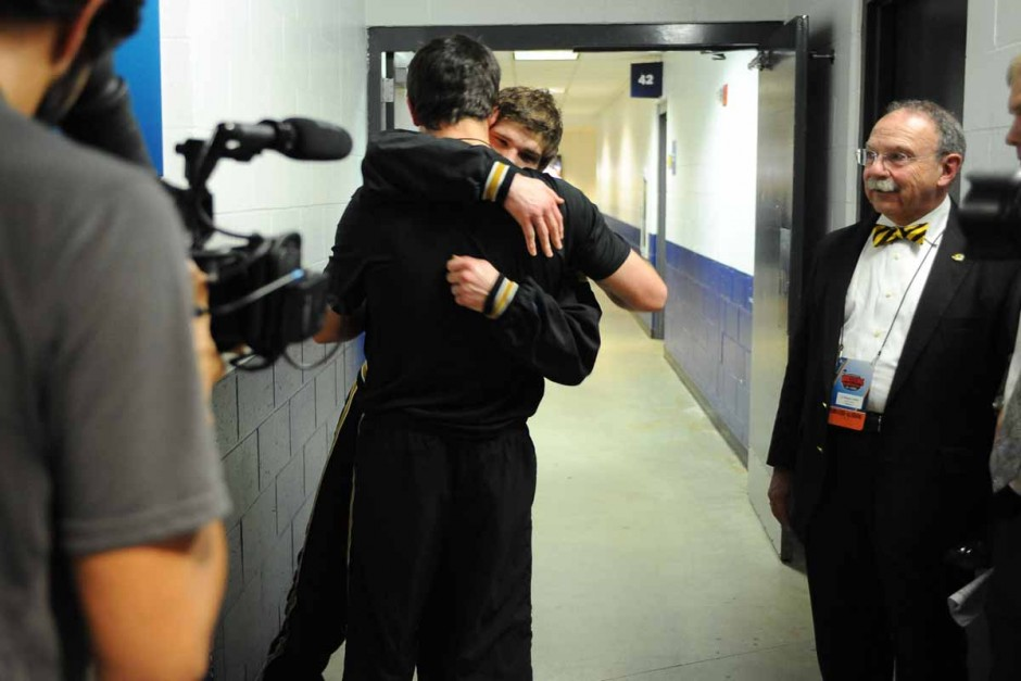 Drake Houdashelt hugs teammate Willie Miklus after finishing his press conference and being congratulated by Chancellor R. Bowen Loftin.