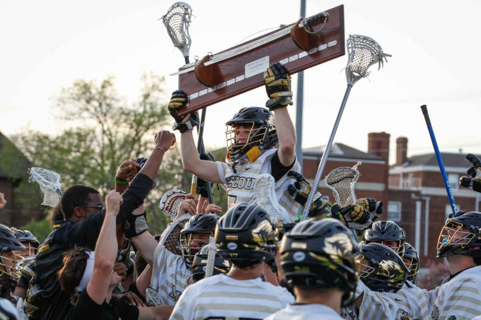 A Mizzou lacrosse player holds the Civil War sword above his head while on the shoulders of his teammates.