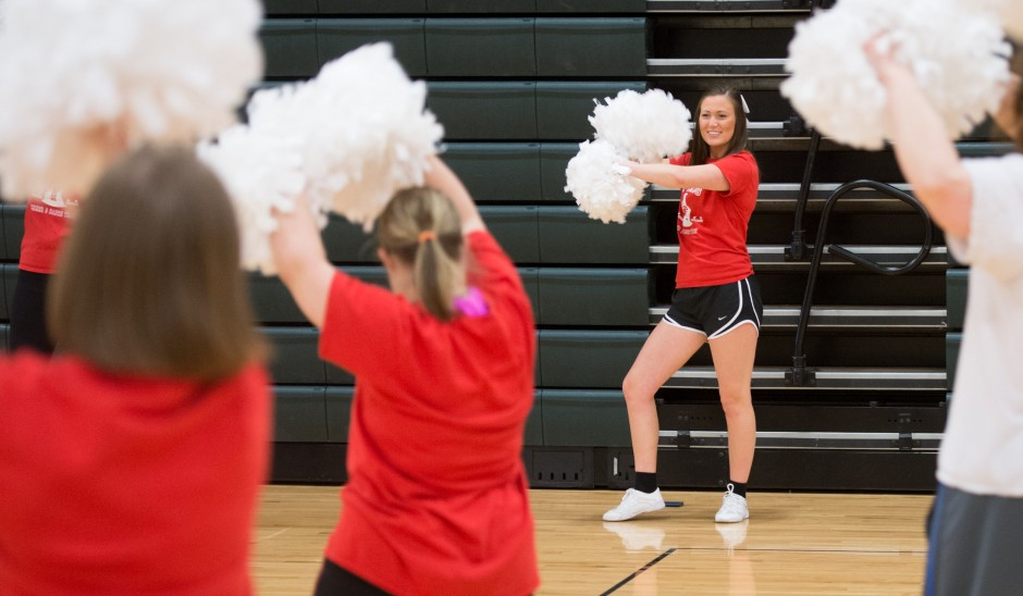 Kelsey Boschert leading a cheer practice with pompoms.