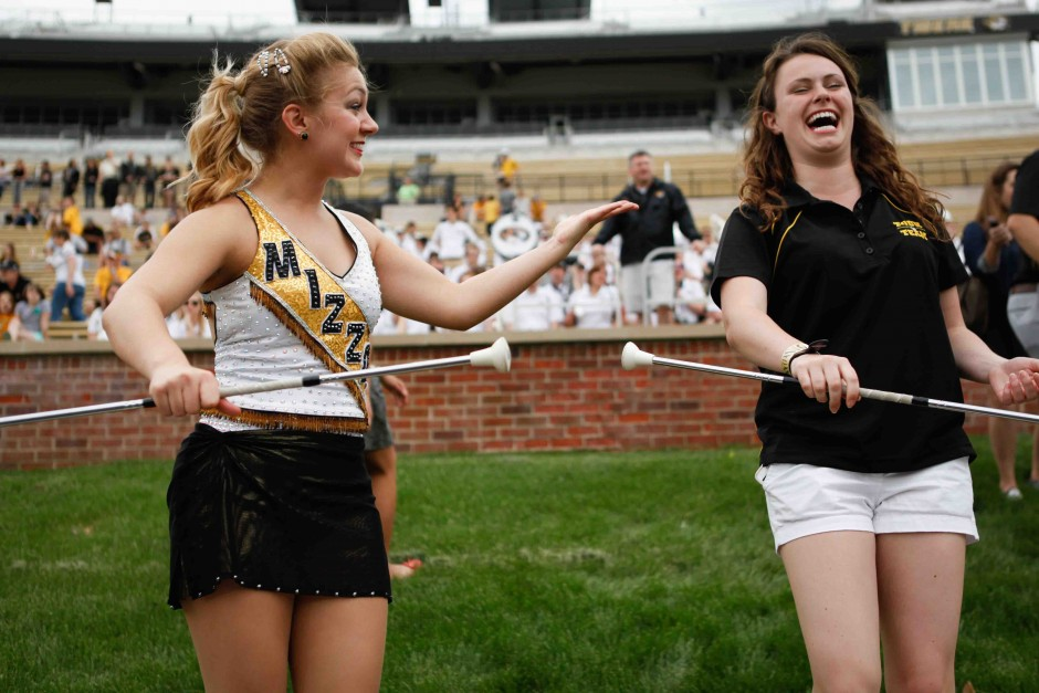 "Halie Hart, Mizzou's Feature Twirler, teaches Samantha Huston, a sophomore Tour Team member, how to twirl a baton on the sidelines before the spring game began. ""You have to twirl it around your thumb! That's the trick."" Hart said."