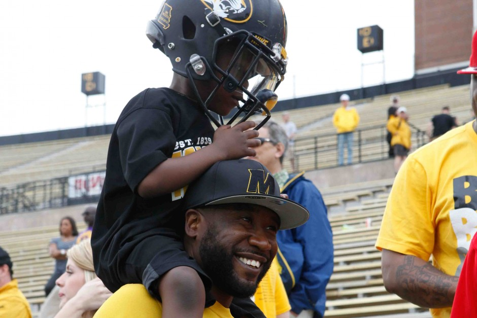 George Penton III sits on his father, George Penton III's, shoulders after the conclusiong of the spring game. Penton III tried on his older brother's helmet for size.