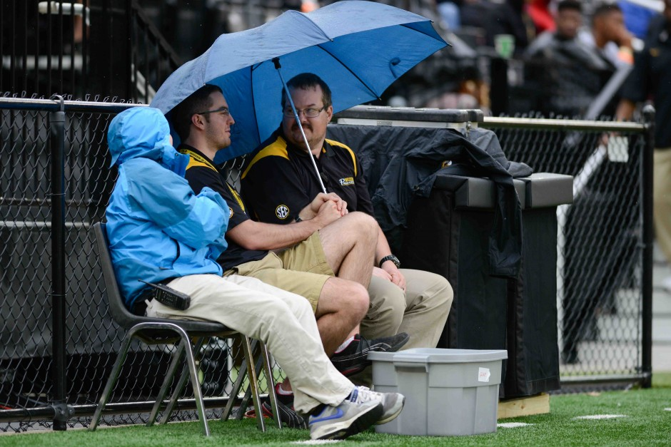 (From left to right): Joe Maddox, Scott Douglas and Chris Barron, members of the production crew, try to stay dry on the sidelines of Faurot field during the spring game.
