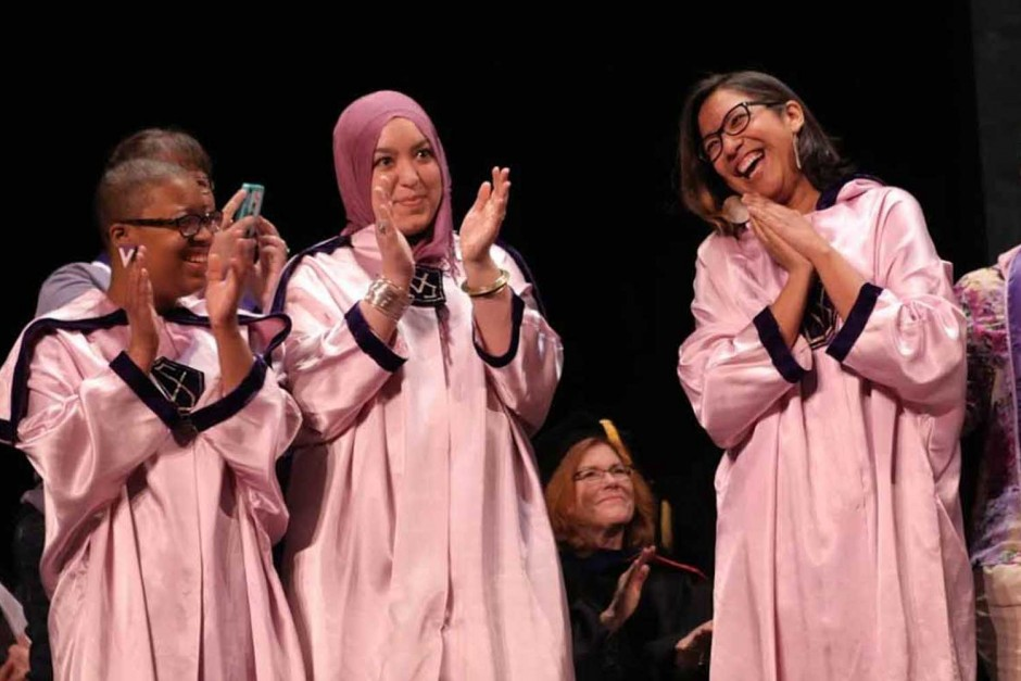Girls in robes clapping.