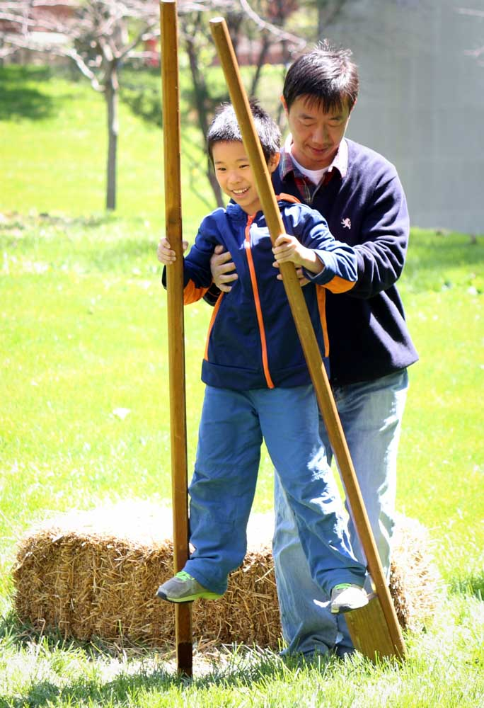Ming (father) and Kevin Wu practice using stilts.