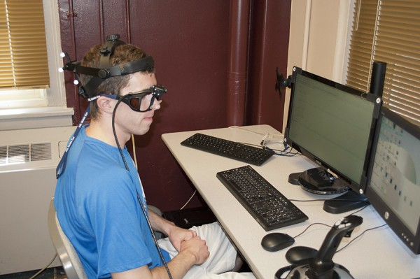 Research subject in goggles at computer screen.