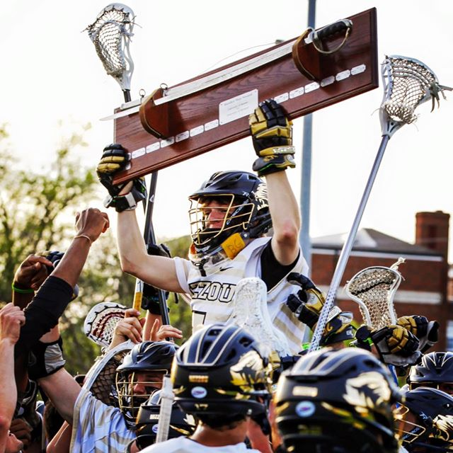Lacrosse player holding trophy.