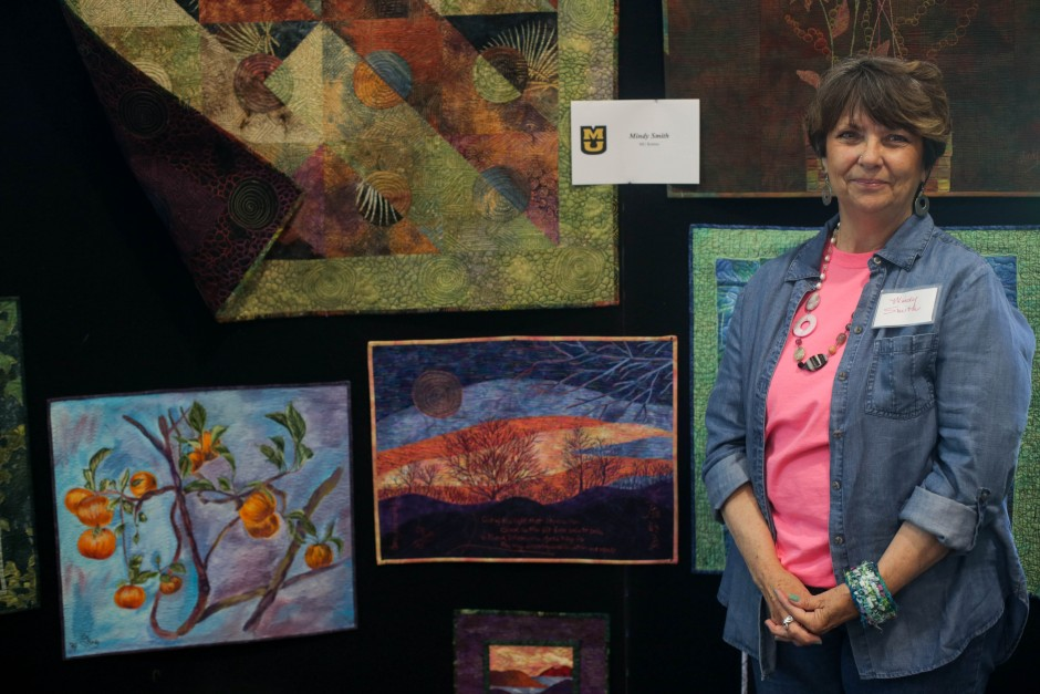 Paintings and fiber art pieces by MU Retiree Mindy Smith stand on display at the 2015 MU Arts & Crafts Showcase. Smith works in a variety of mediums ranging from handmade paper and water color to fabrics and dye.
