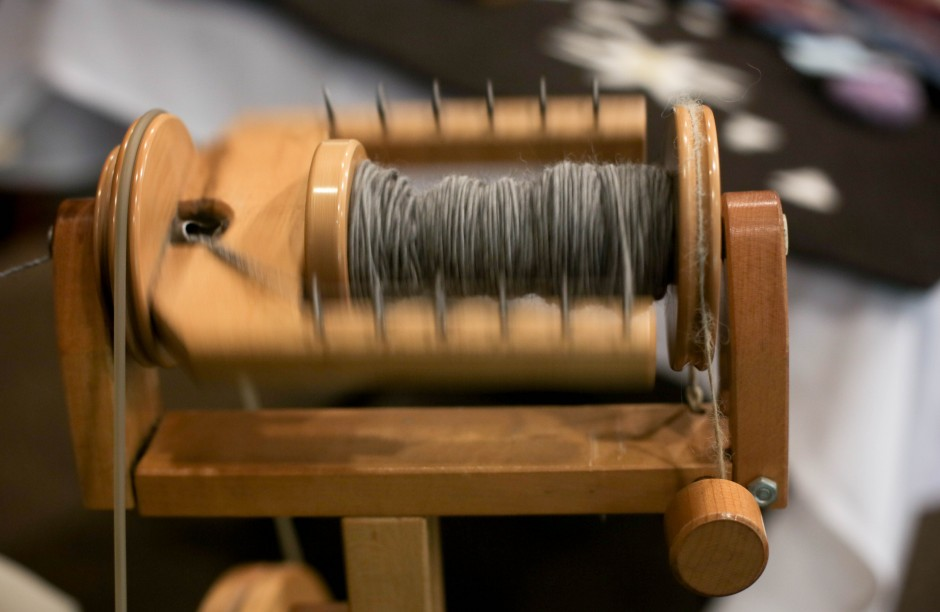 Linda Coats, from MU Career Planning and Placement spins Alpaca fiber into yarn. Coats said it takes approximately one hour to fill a single spool. After she has filled two spools, she then turns the wheel the other way and spins them together to create two-ply yarn, which is much stronger.