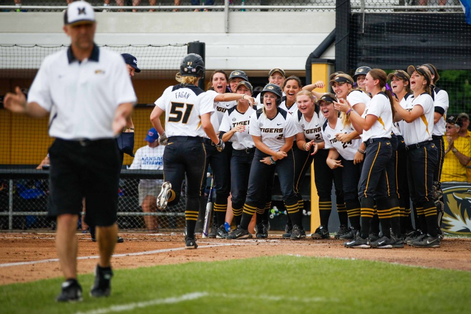 The Mizzou softball team rushes onto the field to welcome Sami Fagan, #51, to home plate, scoring a second run for the Tigers against Kansas. Fagan and Emily Crane, #2, ran home in a single play, scoring two points for Mizzou during the first inning of the game.