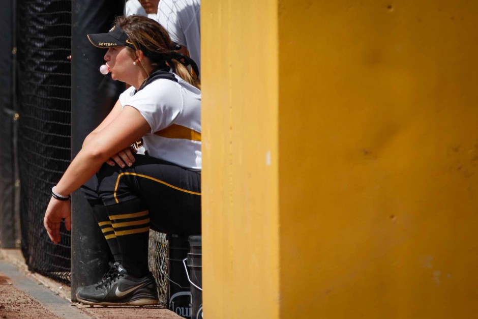 A team member blows bubbles with her bubble gum while watching the game from the dugout.