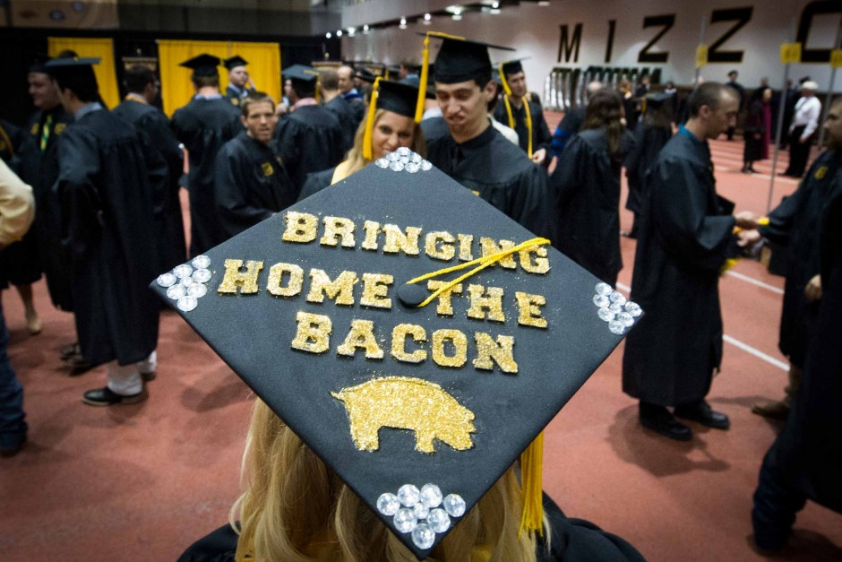 Rachel Bardot, an animal sciences major, takes a picture of her friends and prepares to bring home the bacon after graduation. Photo by Shane Epping.