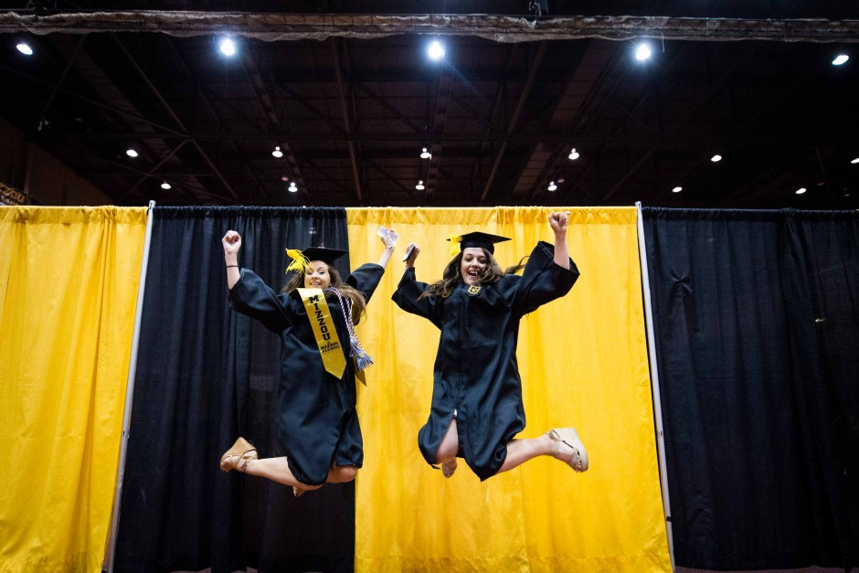 Caroline Bequette and Michelle Sterkowicz, both hospitality management majors, jump for joy.