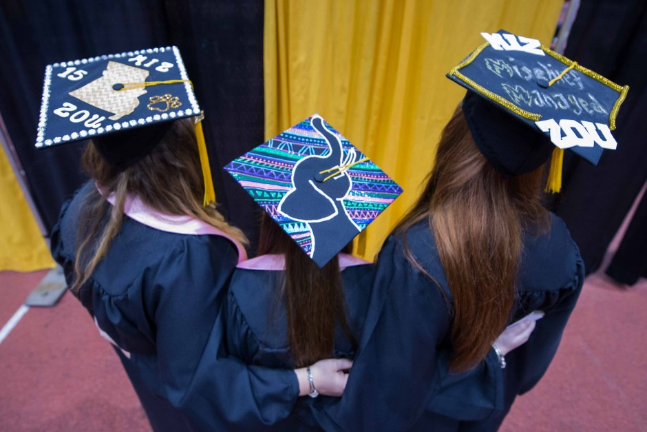 Three College of Agriculture, Food and Natural Resources (CAFNR) to-be graduates show off their caps.