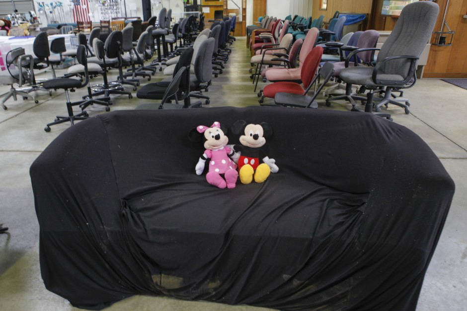 Minnie Mouse and Mickey Mouse cuddle together on a covered couch next to rows of office chairs in Mizzou's Surplus Property warehouse Wednesday, May 20, 2015. The dolls, couch and chairs will all be up for purchase at the Tiger Treasures Rummage Sale on Saturday, May 30 between 6:00 a.m. and 11:00 a.m.