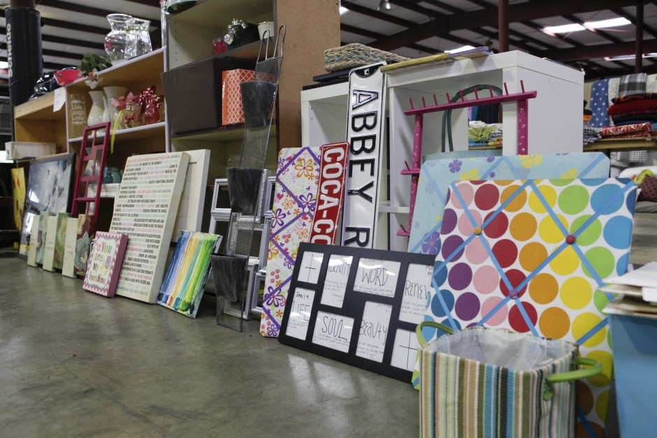 Picture frames, door signs, tack boards and more are assembled around shelves and desk furniture in preparation for the Tiger Treasures Rummage Sale in the warehouse of Mizzou's surplus property.