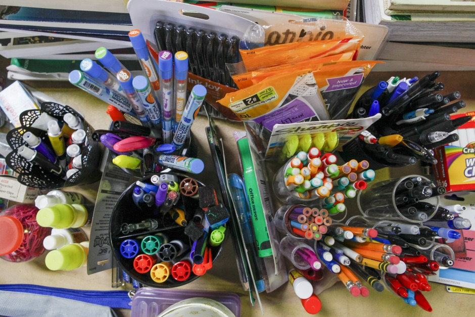Pens, pencils, Sharpie markers and erasers are organized in pencil holders alongside notebook paper and other desk supplies in preparation for the Tiger Treasures Rummage Sale which will be held on Saturday May 30, 2015.