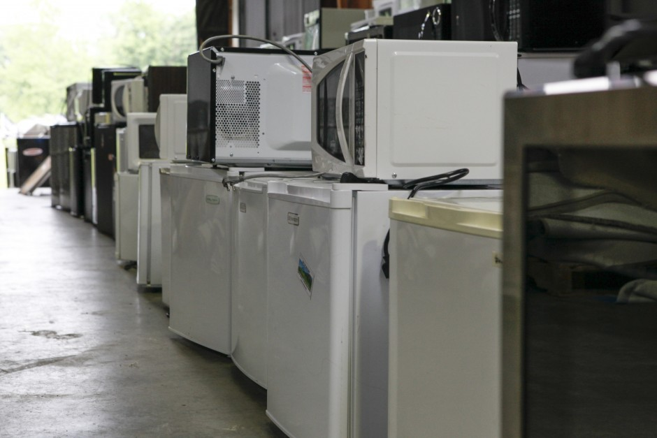 Mini-refrigerators sit underneath microwaves by a loading dock area in Mizzou's surplus property warehouse on Wednesday, May 20, 2015.