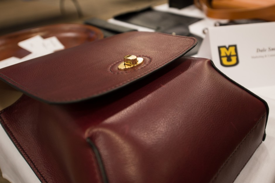 Mizzou Creative employee Dale Smith fills his table with handmade leather goods.