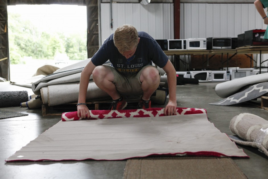 "Dan Meyer, a senior education major, begins to roll up a rug before adding it to the pile of other rugs that will be for sale during the Tiger Treasures Rummage Sale on Saturday, May 30, 2015. ""The most rewarding part is the end goal - kids going to camp!"" Meyer said. Money raised during the rummage sale will be used as scholarship funds for families looking to send their children to the YMCA's Camp Mudd who need help paying for the $140 per week fee."