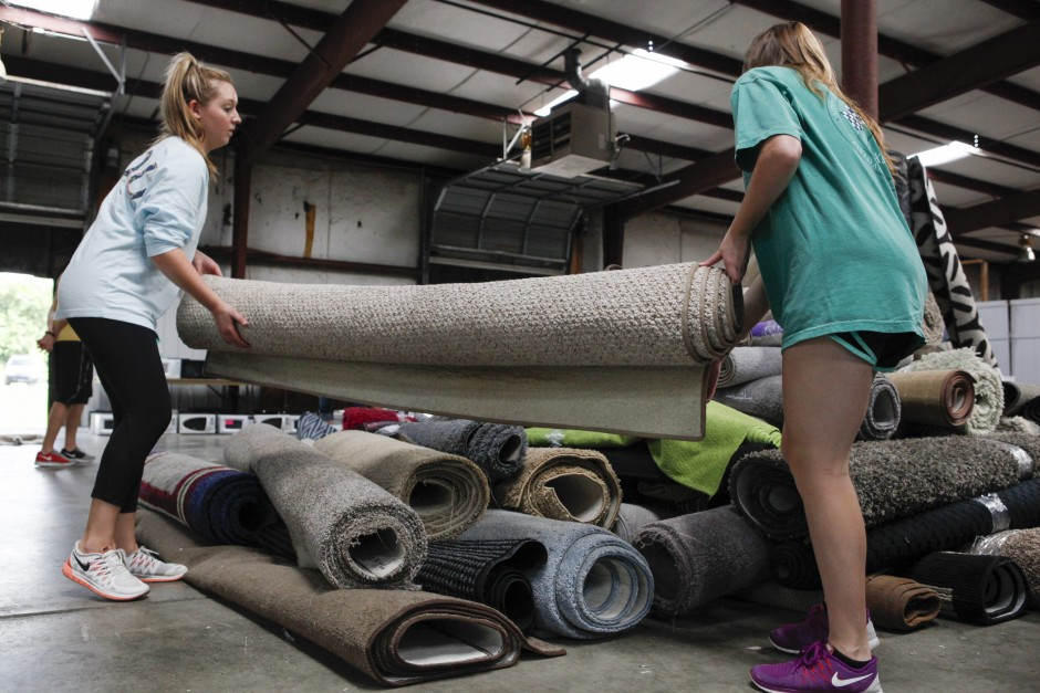 "(From left to right): Paige Burroughs and Abby Michel, sophomores, help each other carry a rug over to the ""to-be-sold"" pile. This summer will be the girls' first time as camp counselors. ""It's amazing that we can accomplish so much in such a short amount of time,"" Michel said. ""This is going to help so many people!"""