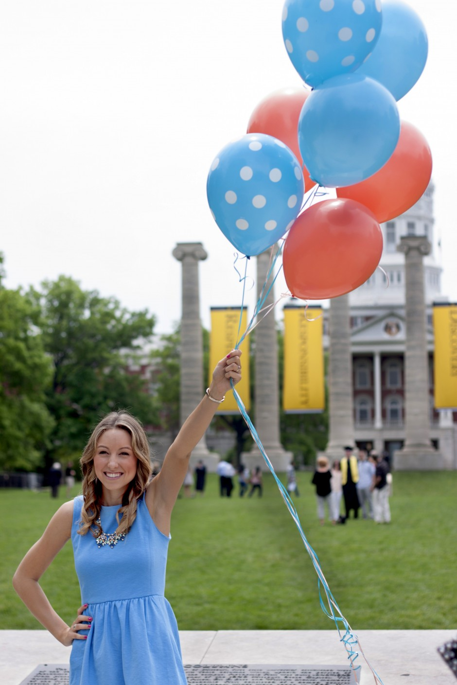 Dana Kaempfe, a newgraduate of the Missouri School of Health Professions, celebrates the occasion with a bundle of balloons and her parents.